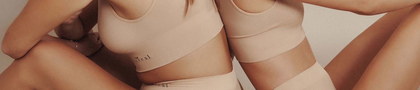two women sitting back to back wearing reveal bra and panty